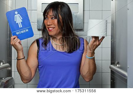 Transgender female in restroom stall, smiling with women's restroom sign in one hand, roll of toilet paper in the other.