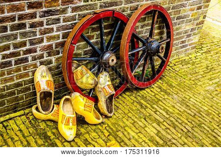 Old yellow painted Dutch Wooden Shoes resting against steel rimmed wooden Wagon Wheels with wooden spokes