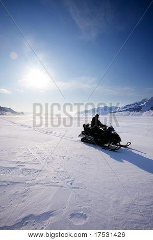 A snowmobile on frozen ice on a barren winter landscape