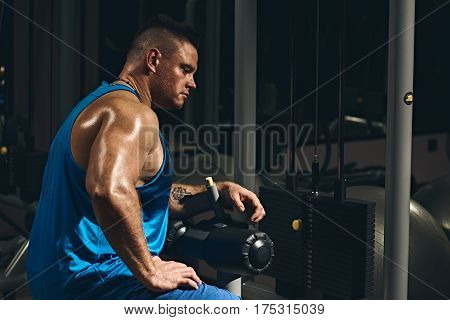 Muscular young bodybuilder man training with dumbbells at gym