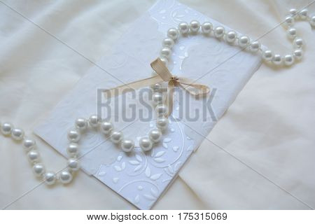 wedding invitation and string of pearls, vintage background