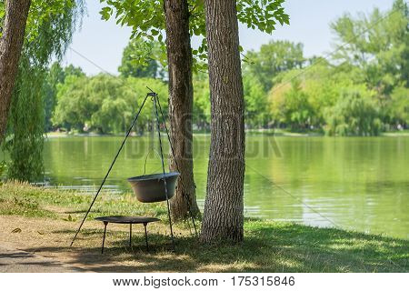 Camping cooking pot near trees and lake