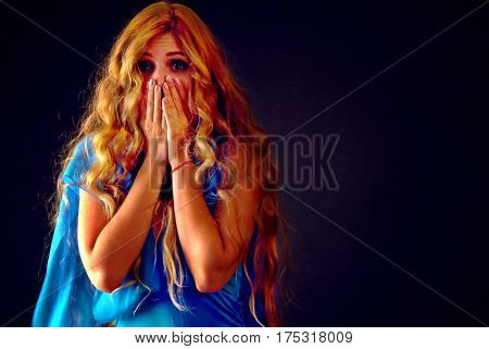 Frightened woman screaming with fear indoor at halloween night. Horror. Girl with tousled long blond hair and opened her eyes wide bawl covered her face on black background.