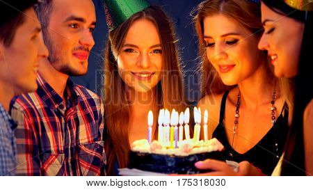 Happy friends birthday celebrating food with candle celebration cakes in club. People wear in hat party looking at burning candles. Youth celebrates together. Women and men have fun.