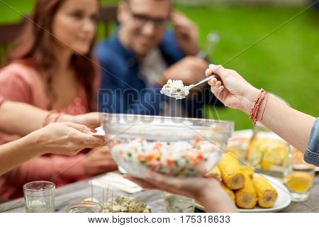 leisure, holidays, eating, people and food concept - happy friends having dinner at summer garden party