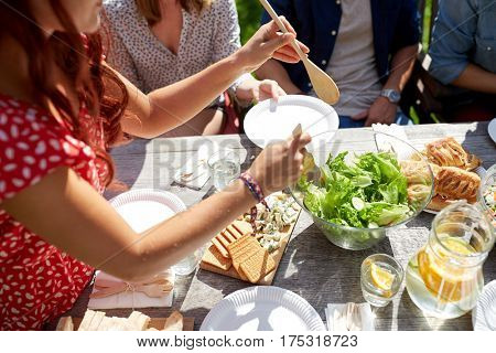 leisure, holidays, eating, people and food concept - happy friends having dinner at summer party