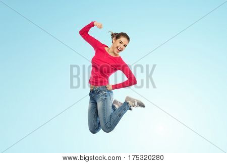 happiness, freedom, power, motion and people concept - smiling young woman jumping in air with raised fist over blue background