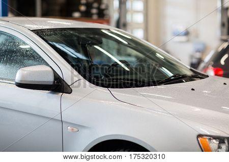 auto service, carwash and maintenance concept - car at repair station