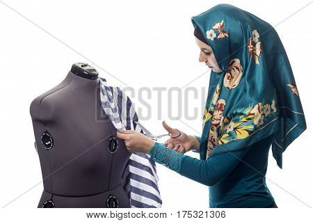Self employed female tailor or fashion designer wearing a hijab. Her outfit is associated with muslim and middle eastern or east european culture. She is isolated on a white background.