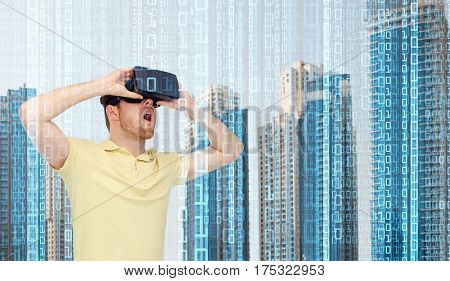 modern technology, cyberspace and people concept - happy young man with virtual reality headset or 3d glasses playing game over city skyscrapers and binary code background