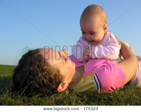 Mother With Baby On Sunset Lie