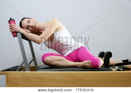 aerobic gym pilates woman rest holding water bottle in reformer bed