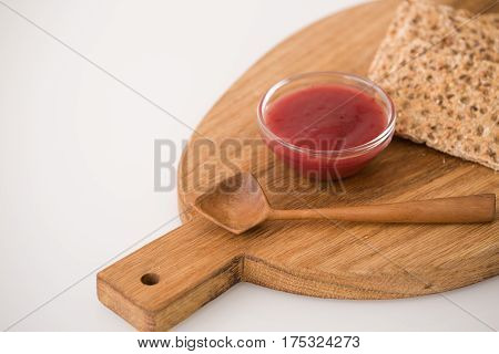 Top view on wooden board with organic wholegrain crisps with strawberry jam on kitchen table. Healthy Breakfast or snack. Healthy food and eating.