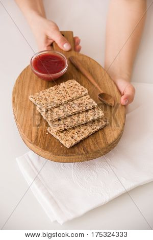 Top view on woman's hands holding wooden board with organic wholegrain crisps with strawberry jam on kitchen table. Healthy Breakfast or snack. Healthy food and eating.