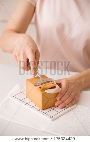 Top view on woman's hands cutting traditional scandinavian organic brown cheese with cheese knife on kitchen table. Healthy Breakfast or snack. Healthy food and eating.