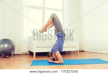 fitness, sport, people and healthy lifestyle concept - woman making yoga in headstand pose on mat