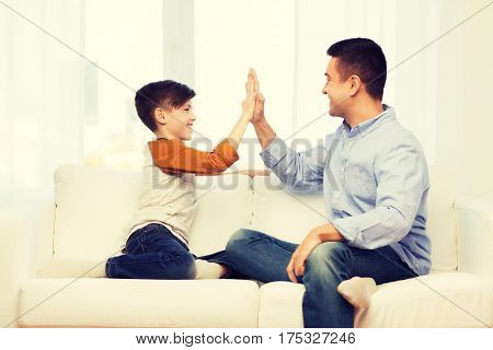 family, gesture, fatherhood, generation and people concept - happy father and son doing high five at home