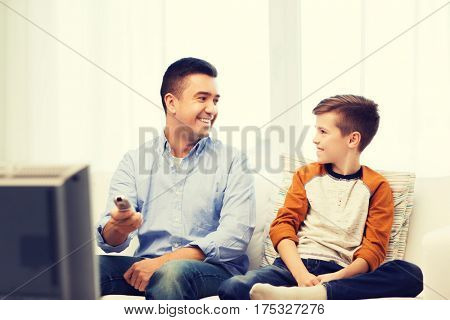 family, people, technology, television and entertainment concept - happy father and son with remote control watching tv at home