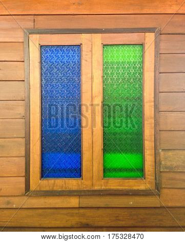 Colorful blue and green glass windows on brown wood wall