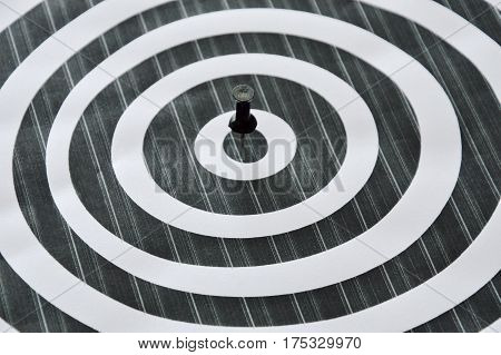 black and white circle with push pin stabbing target