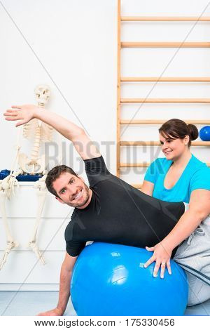 Young man exercising on swiss ball in physiotherapy