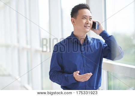 Cheerful Singaporean entrepreneur standing at window and calling on phone