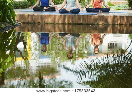 People meditating by pond, reflection in water