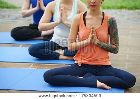 Cropped image of three people meditating together