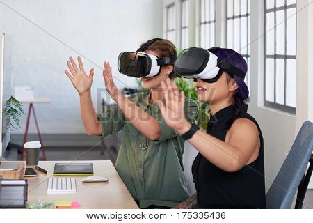 Asian woman showing her colleague her new project using virtual reality headsets, modern innovative architecture firm