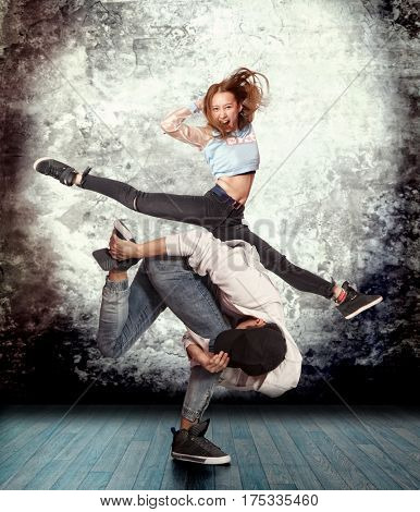 Young couple break dancing on wall background