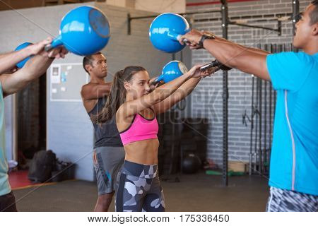 Dedicated and strong kettlebell workout training multiethnic class, led by trainer instructor