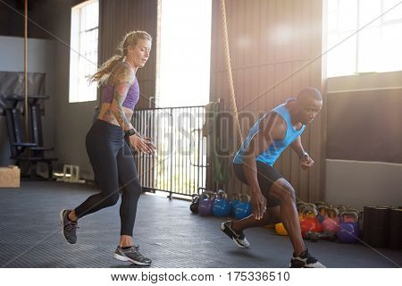Man and woman sprinting in gym for intense training session