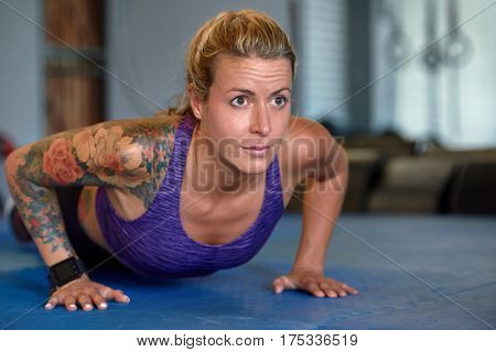 Strong young woman with tattoos doing push up exercise in gym