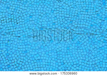 Wall covered with mosaics of white and light blue color with gray cement seams