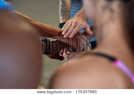 Diverse group of friends stacking their hands in a circle, teamwork working together concept