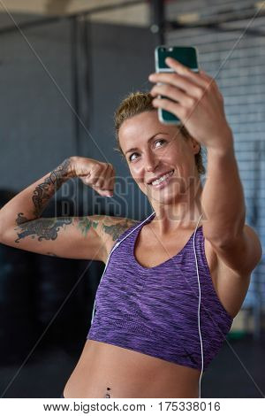 attractive confident fit woman flexing her bicep while taking a selfie on phone in sports bra at gym