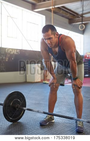 Portrait of fit healthy man resting between weight lifting sets, active lifestyle crossfit training