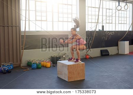 Young fit woman doing box jumps in industrial gym, good form posture technique