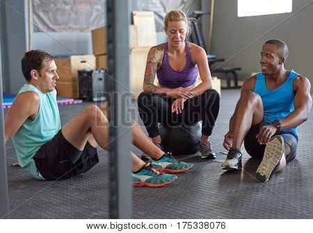 Diverse multiethnic group of people taking a break while exercising between sets in gym