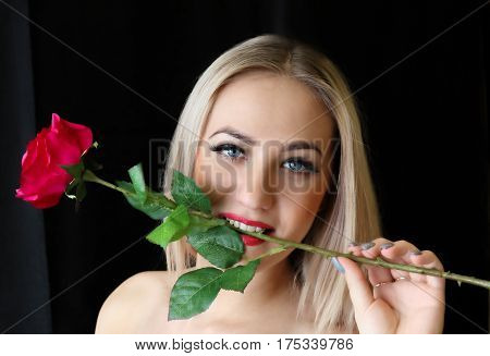 beauty yuong blond woman in dress on black background with a rose in his mouth