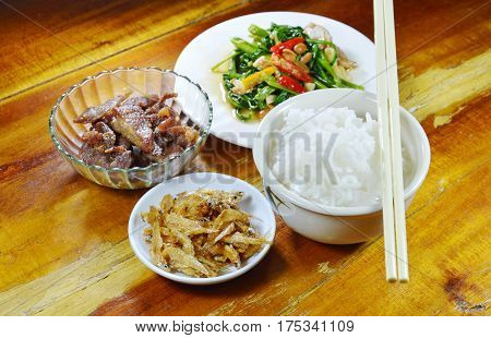 boiled rice eat with fried anchovy and morning glory on table