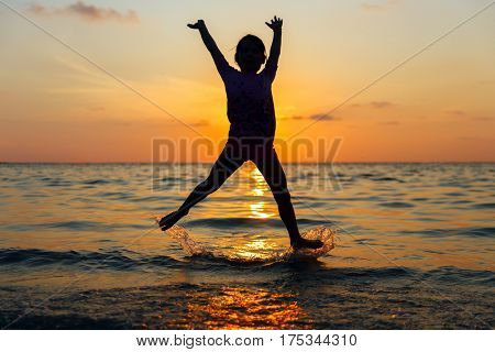 Happy little girl having fun, swimming and jumping at shallow water