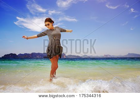 Beautiful girl enjoying the nature in the tropical sea waves