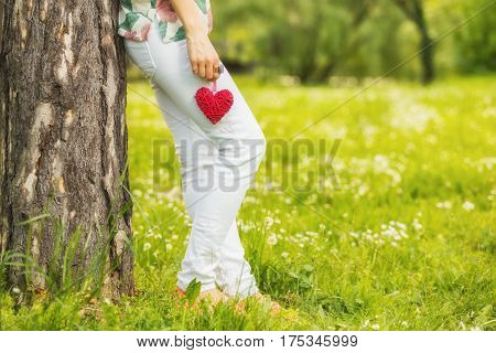 Lonesome girl holding a heart in the park.