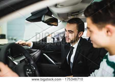 Let me show you interior of this car. Handsome young classic car salesman standing in the dealership and helping a client to make a decision about car