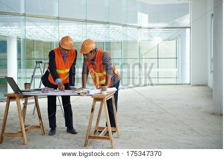Investor explaining plan of building to contractor