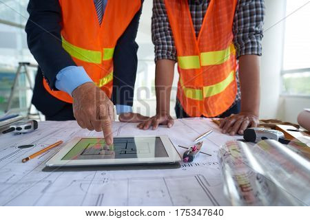Architect showing building plan on tablet computer to his coworker
