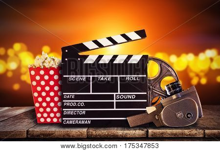 Retro film production accessories placed on wooden planks. Concept of film-making. Blur spot lights on background