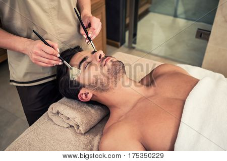 Close-up of young man lying down on massage bed during traditional Chinese facial treatment at Asian beauty center