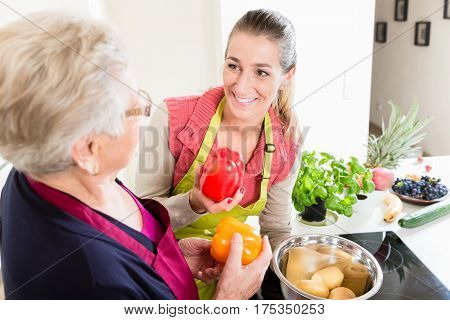 Mother in law explaining correct use of bell pepper in kitchen to her daughter in law once again